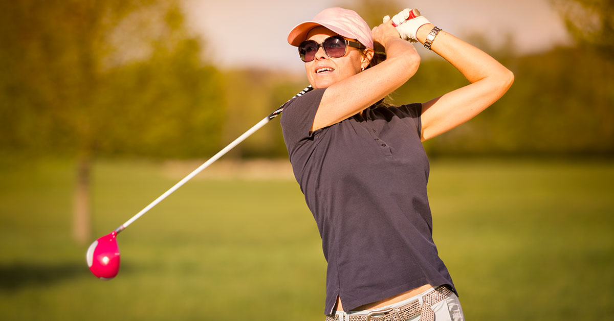 Woman Swinging Pink Golf Club Properly To Prevent Common Golf Injuries