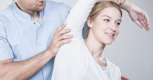 Chiropractor Stretching A Woman's Shoulder   Common Conditions Treated By Chiropractors   Upstate Spine & Sport