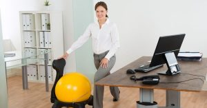 Woman Stretching Next To Desk With Exercise Ball Chair | Relieve Back Pain From Sitting